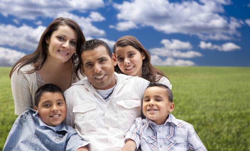 Shappy Hispanic Family Portrait Sitting in Grass Field royalty free stock photo