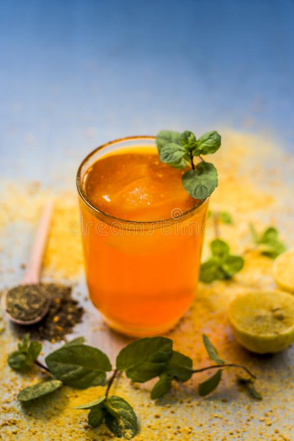 Sharbat of orange with black pepper powder,mint leaves,and a pinch of slat on silver wooden surface royalty free stock photo