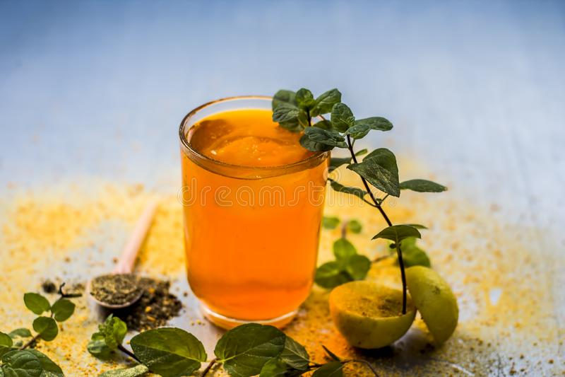 Sharbat of orange with black pepper powder,mint leaves,and a pinch of slat on silver wooden surface royalty free stock image