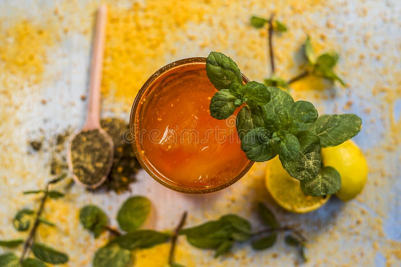 Sharbat of orange with black pepper powder,mint leaves,and a pinch of slat on silver wooden surface stock photos