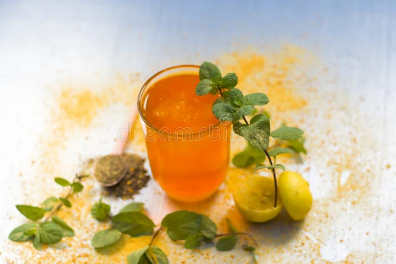 Sharbat of orange with black pepper powder,mint leaves,and a pinch of slat on silver wooden surface stock image