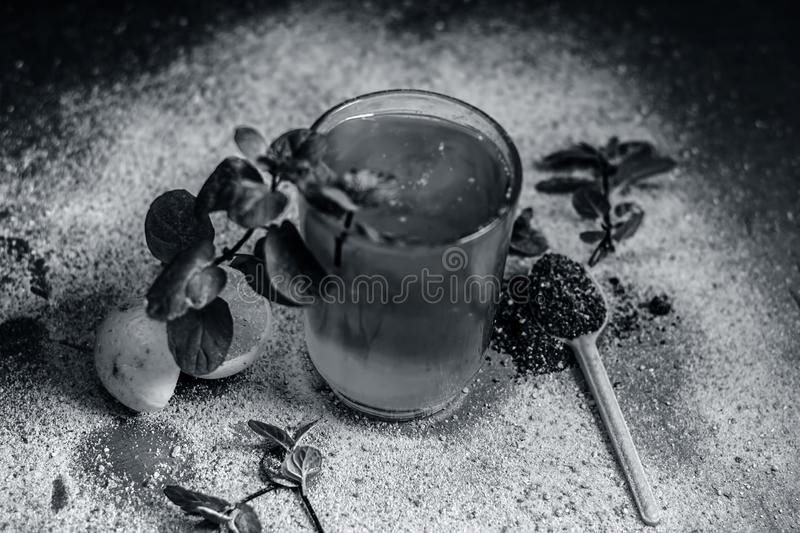 Sharbat of orange with black pepper powder,mint leaves,and a pinch of slat on silver wooden surface stock photography