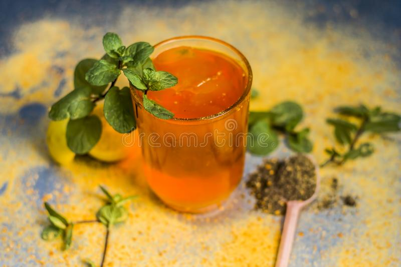 Sharbat of orange with black pepper powder,mint leaves,and a pinch of slat on silver wooden surface stock images