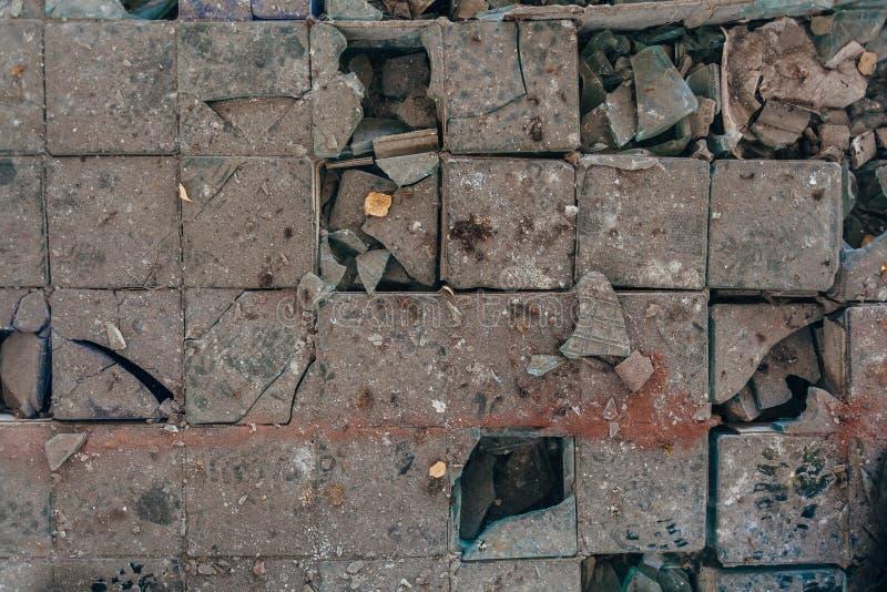 Shards of broken glass block panel on dirty floor.  stock photography