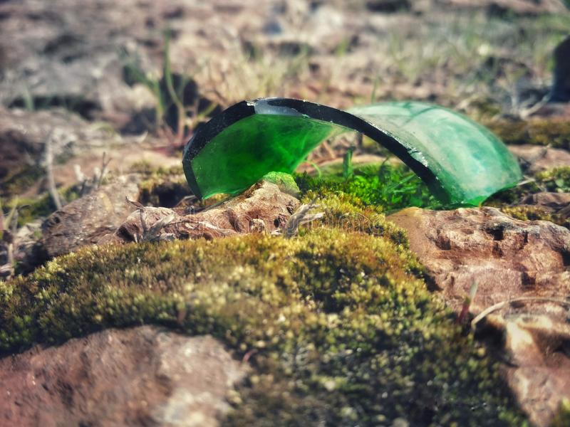 Shards of green glass on gray stones on a sunny day stock photography