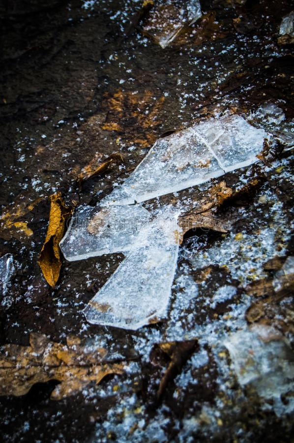 Shards of ice. Broken ice on bare earth. Winter photo. Pieces of cold ice, like glass stock image