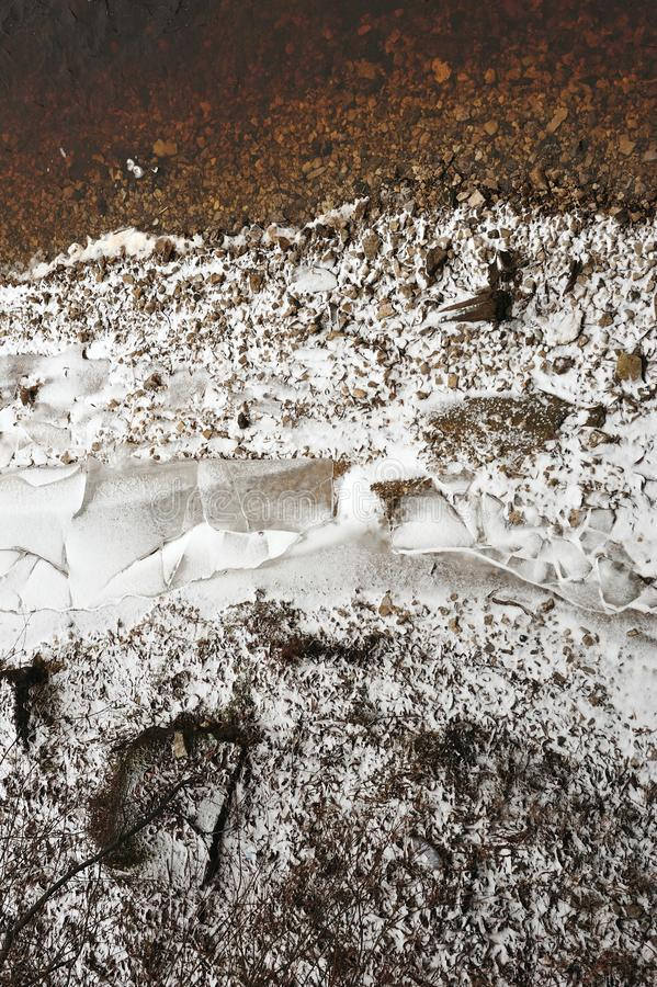 Shards of ice. On the stone bank of the river in late autumn royalty free stock photography