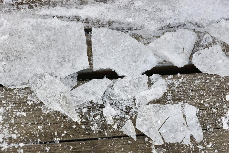 Shards of ice on wooden boards texture background. Large pieces and small pieces stock photography