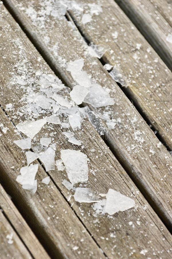 Shards of ice on wooden boards texture background. The puzzle of the various pieces of ice. cold in human relations psychology royalty free stock photography