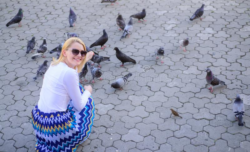 Share generosity. Girl blonde woman relaxing city square and feeding pigeons. Woman tourist or citizen toss crumbs for royalty free stock photography