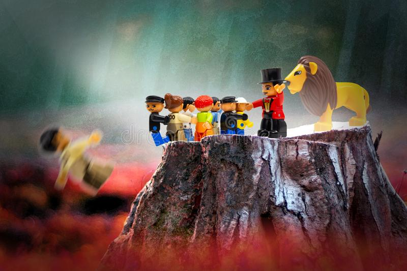 Share the planet concept. Composite image using plastic toy figures. A crowd of people are curious about the exotic lion, which is guarded by a tamer. They all stock photo