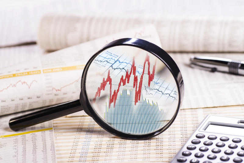 Share Prices. Magnifier sorrounded by several papers with course tables shows the course of stock prices stock photos