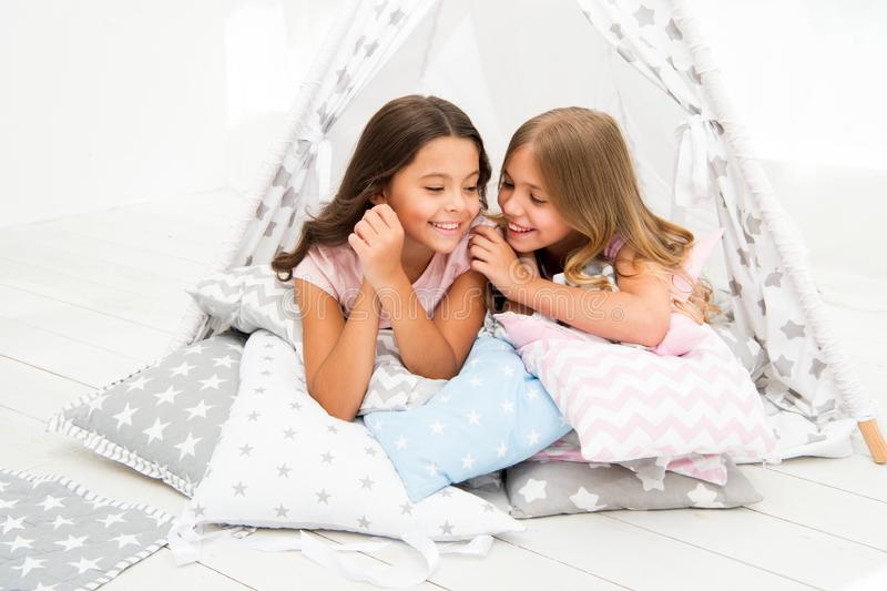 Share secrets concept. Girls cute children lay relaxing in teepee bedroom. Cute space for leisure. Modern interior. Includes comfortable teepee houses. Secret stock images