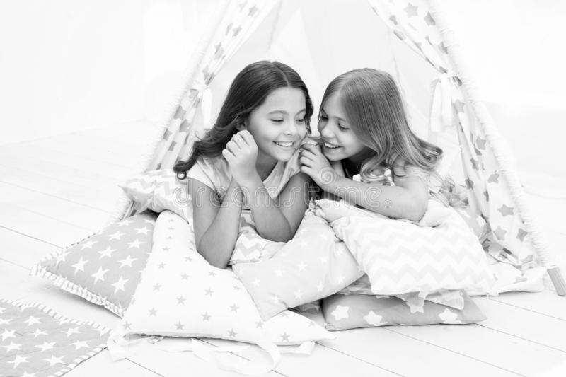 Share secrets concept. Girls cute children lay relaxing in teepee bedroom. Cute space for leisure. Modern interior. Includes comfortable teepee houses. Secret royalty free stock photography