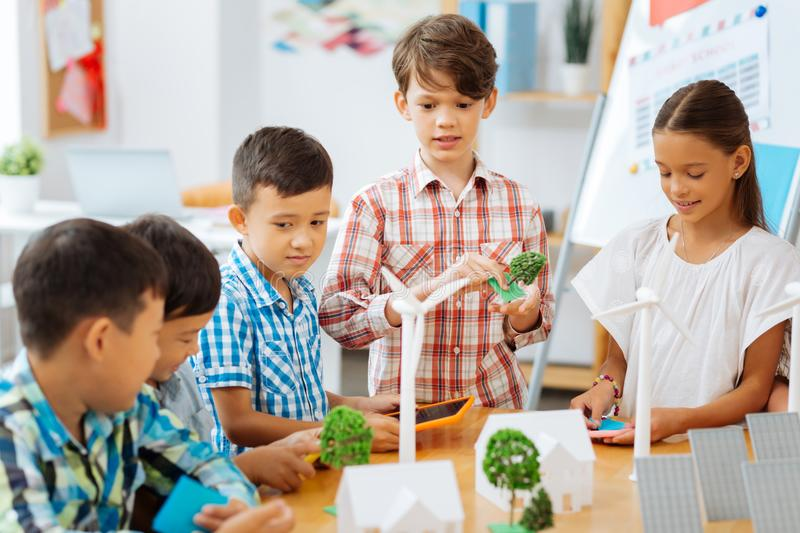 Thoughtful children dicsussing the task in a classroom. Share your ideas. Thoughtful children discussing the task while sitting in a classroom royalty free stock photography