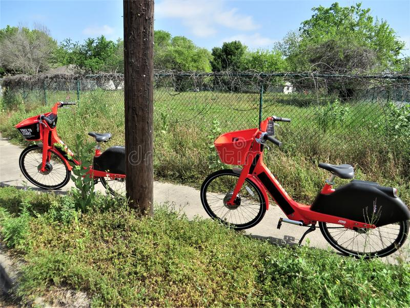 Shareable electric bikes, Austin. Pair of red electric bikes left at street corner in east Austin by overgrown vacant lot. Scattered throughout the city they are stock photo