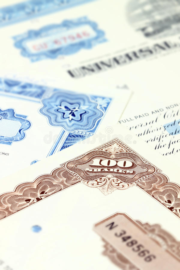 Shares. 100 shares. Old stock share certificate. Vintage scripophily objects. Shallow depth of field royalty free stock image