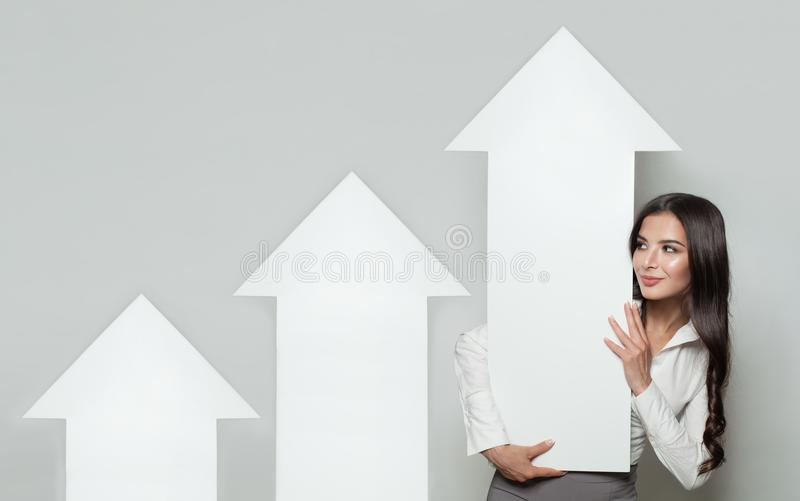 Shares Up, Business Success and Profit Concept. Smiling Business Woman with White Empty Rising Arrows stock image