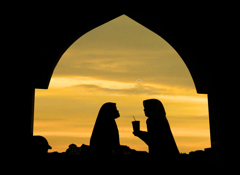 Sharing. Islamic woman infront a mosque sharing a cup of drink royalty free stock images