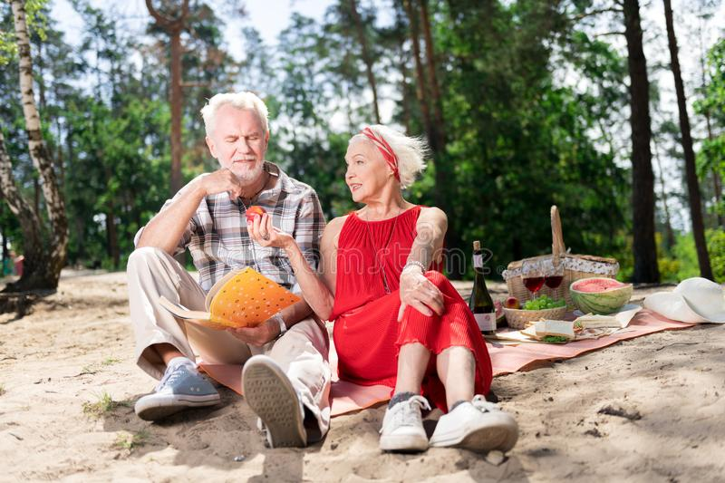 Caring elderly wife sharing her apple with husband during picnic royalty free stock images