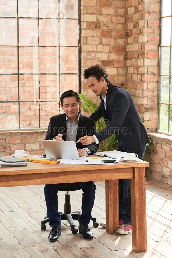Sharing business data. Businessman showing information on laptop screen to coworkers stock images
