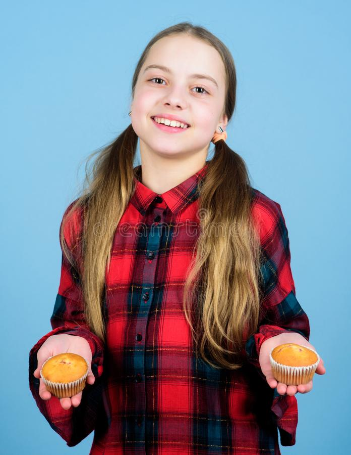 Sharing cakes for two. Happy little girl holding fairy cakes. Small child happy smiling with cup cakes. Cheerful kid stock photo