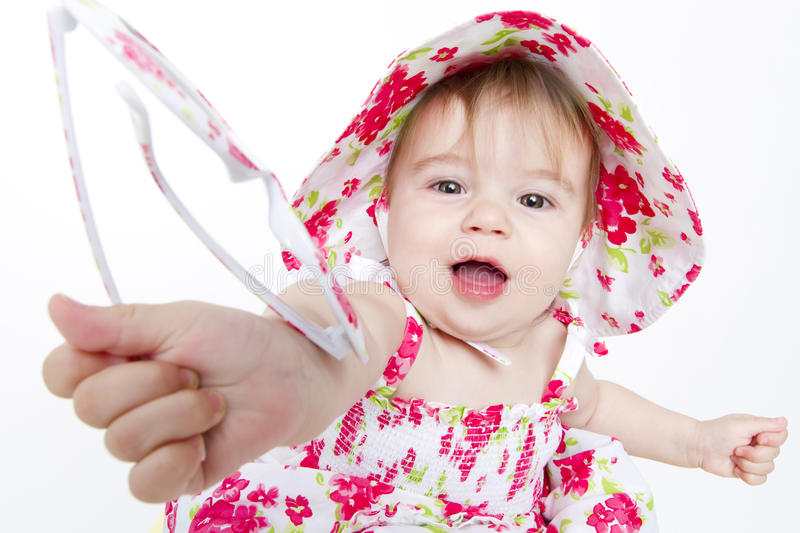 Sharing is Caring. Little baby girl with pretty red flower dress and hat handing over her sun glasses to you royalty free stock photo
