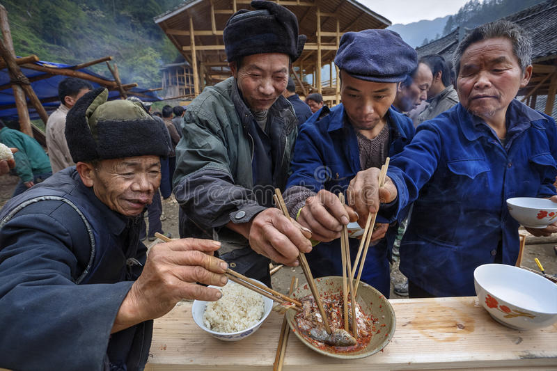 Sharing food at village festival, villagers celebrate beginning. Langde Village, Guizhou, China - April 16, 2010: Festive ceremony of the start of construction royalty free stock photography