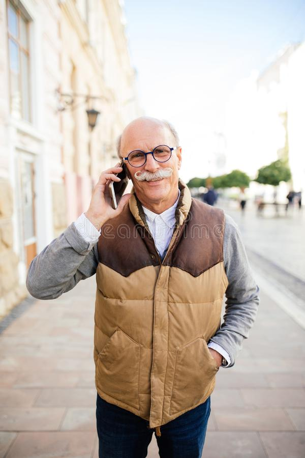 Sharing good news. Handsome senior man talking on the mobile phone and smiling in the city street. stock photography