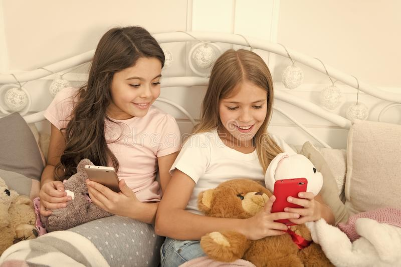 Sharing great pictures. Merry Christmas and Happy New Year greetings. Little girls use smartphone in bed. Happy little royalty free stock photos
