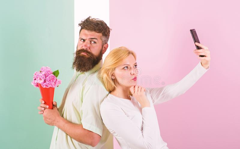 Sharing happy selfie. Woman capturing happy moment boyfriend bring bouquet flowers. Capturing moment to memorize. Taking. Selfie photo. Couple in love bouquet royalty free stock photography