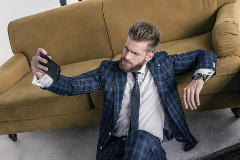 Amaizing look. Top view handsome young man in full suit taking selfie while sitting on the floor at home stock photos