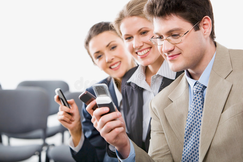 Sharing info. Portrait of young businesspeople sharing info on mobile phones in the room stock photo