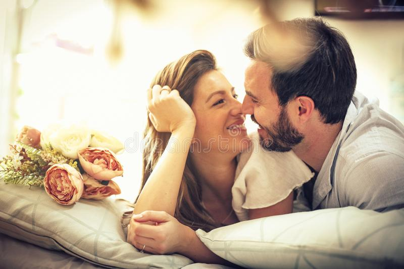 Sharing love. Young happy couple in bed. Space for copy royalty free stock photography