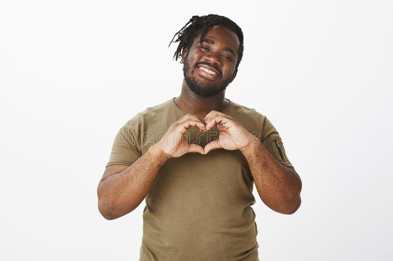 Sharing love and warm emotions with girlfriend. Portrait of happy carefree african male friend in olive t-shirt, smiling stock photography