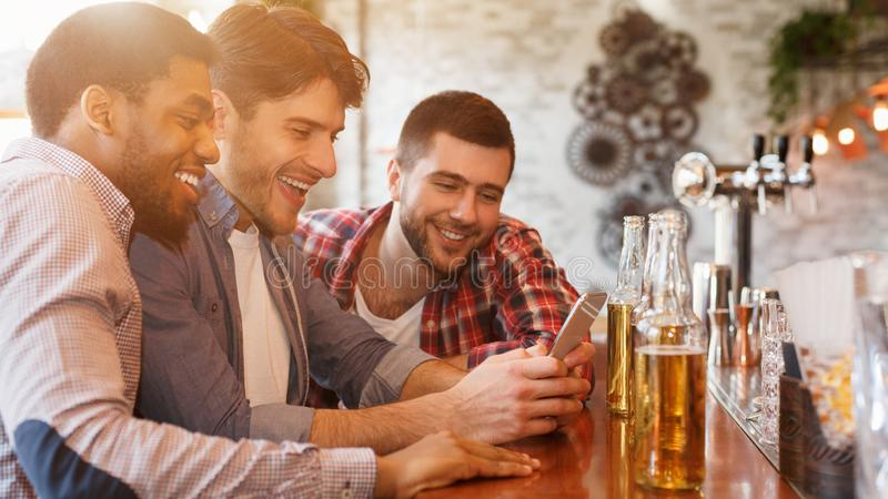Sharing News With Smartphone And Drinking Beer In Bar stock images