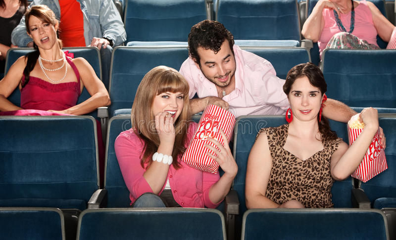 Sharing Popcorn In A Theater Royalty Free Stock Photo