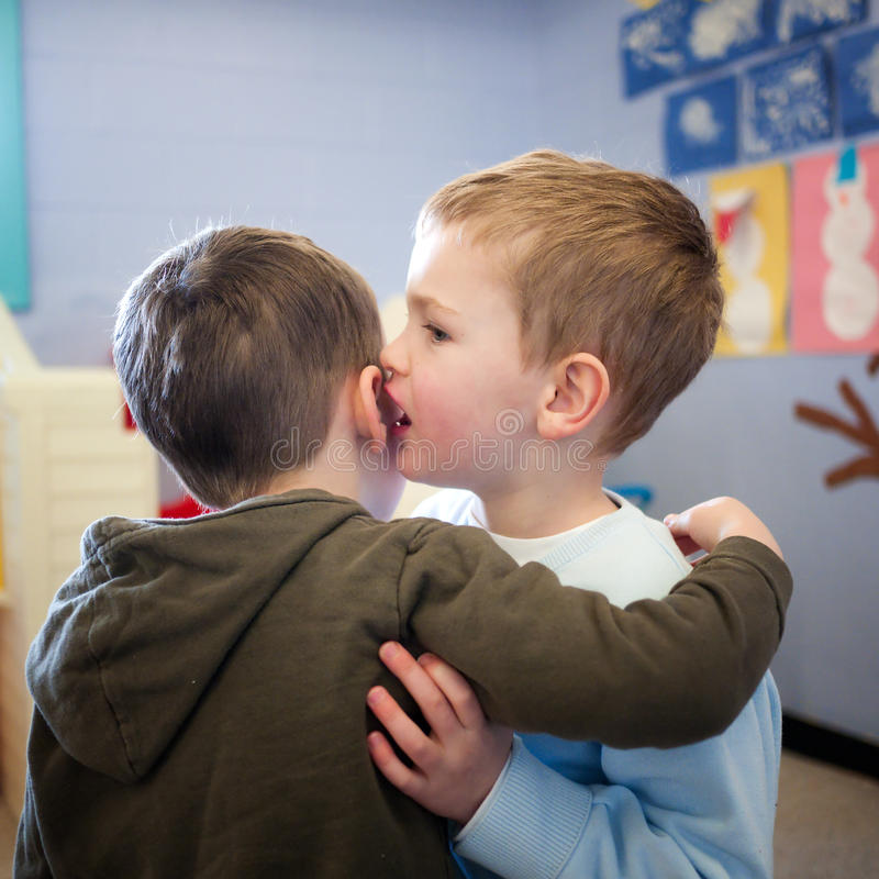 Sharing a secret. Two boys sharing a secret in school classroom stock photos
