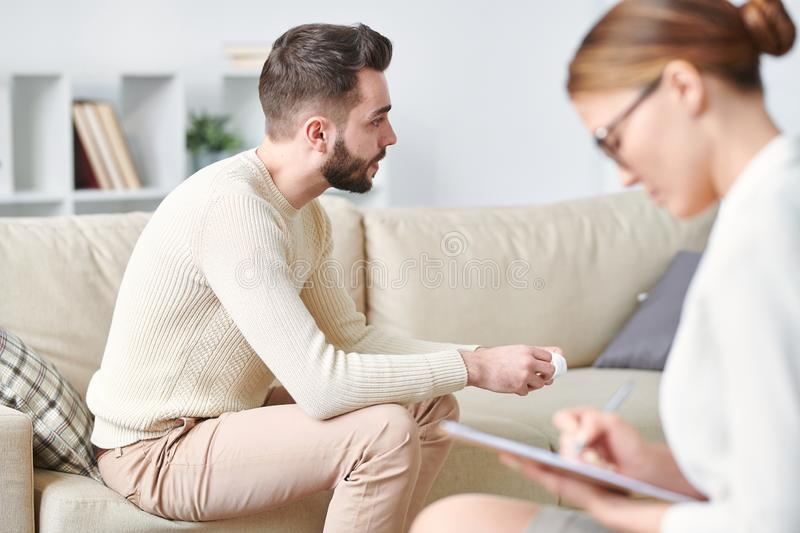 Sharing troubles. Troubled and upset patient of counselor sitting on couch and telling his story while psychologist making notes royalty free stock images