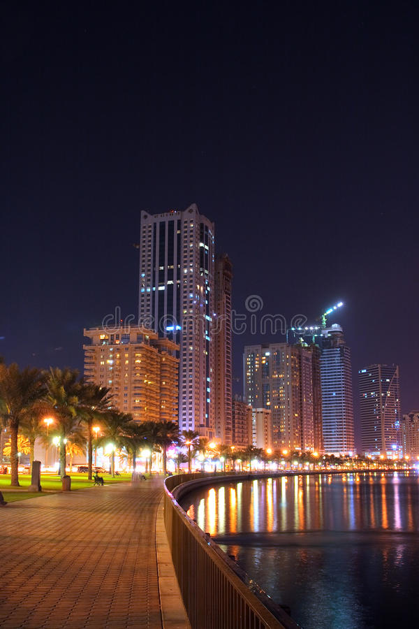 Sharjah Corniche Road at Night, Abu Dhabi. Sharjah Corniche Road, United Arab Emirates. City Park and Downtown Skyscrapers at Night royalty free stock photography