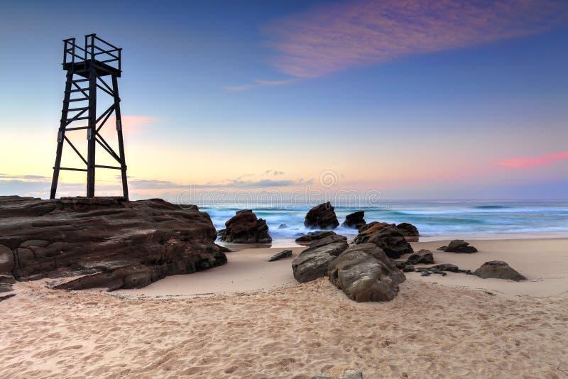 Shark Watch Tower and jagged rocks Australia. The Shark Tower and jagged rocks at Redhead Beach, NSW Australia royalty free stock photo