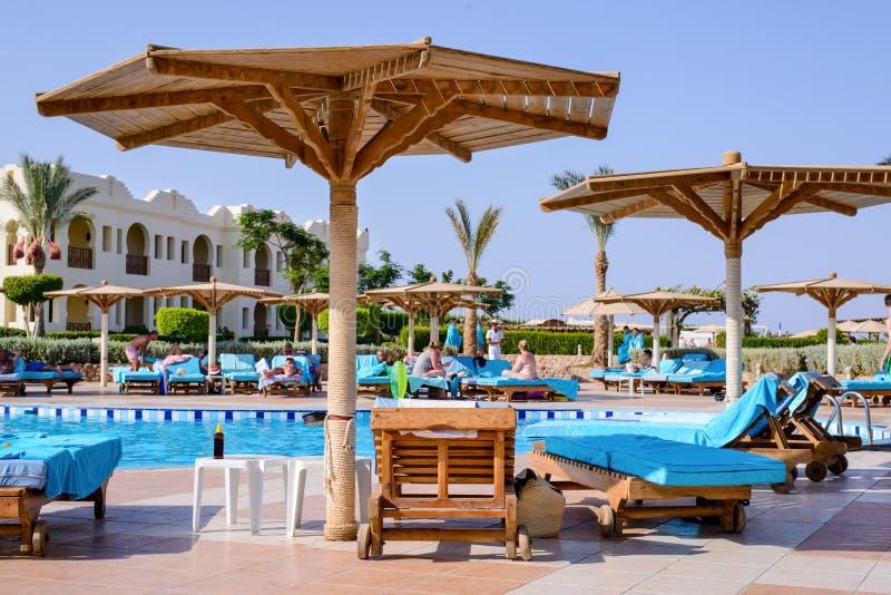 Sharm El谢赫,埃及, 2015年7月28日:在游泳池附近的沙滩伞 免版税库存照片