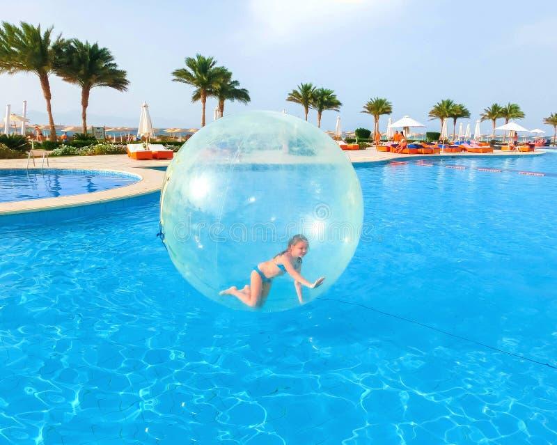 Sharm El谢赫,埃及- 2017年4月09日:一个可膨胀的气球的小女孩,获得在水的乐趣 免版税库存照片