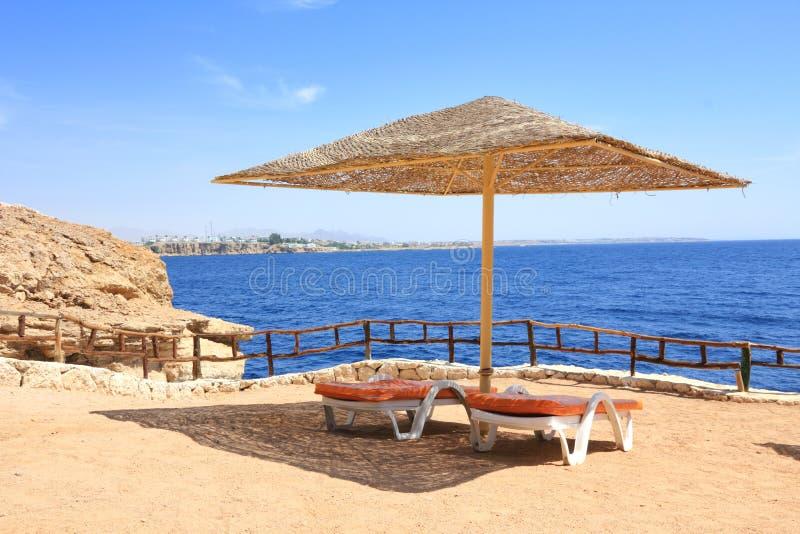 Sharm El Sheik resort. Beach umbrella in Sharm El Sheikh with sea in background royalty free stock photo