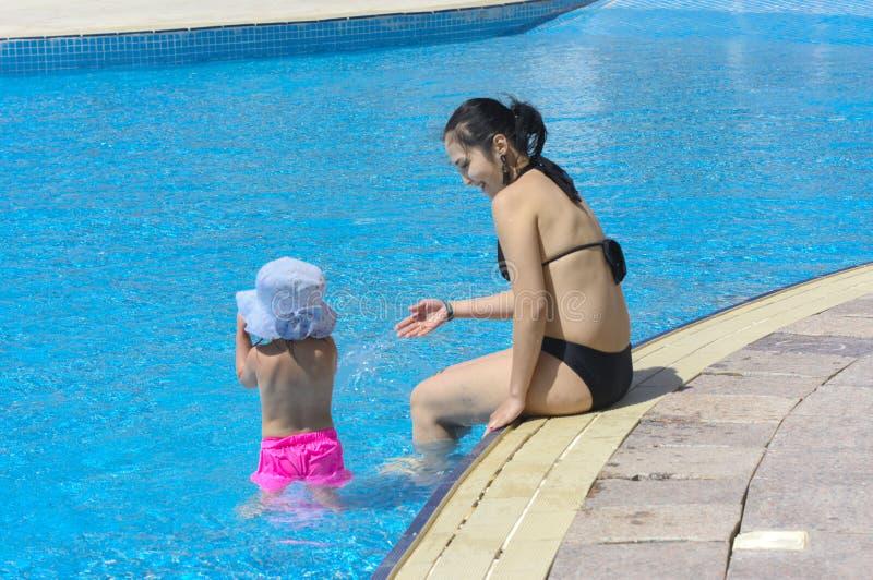 Sharm El-Sheikh, Египет - 14-ое марта 2018 Маленькая девочка с ее матерью в бассейне на предпосылке моря и голубого неба стоковое изображение rf