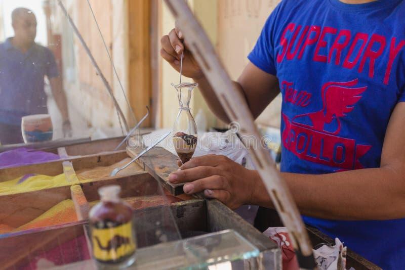 SHARM EL SHEIKH, ЕГИПЕТ - 16-ОЕ МАЯ 2018: Взгляд крупного плана взрослого человека делая сувениры стоковое изображение rf