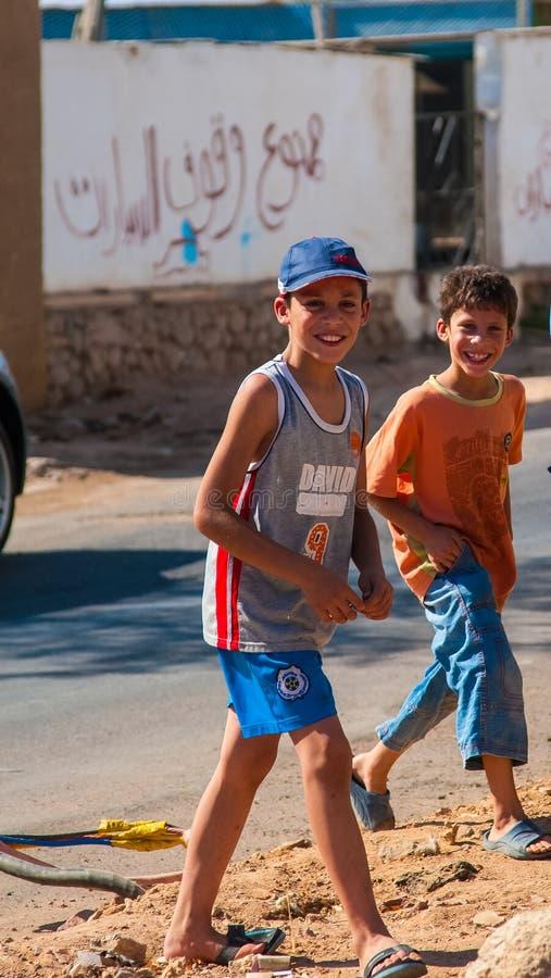 SHARM EL SHEIKH, EGIPTO - 9 DE JULHO DE 2009 Meninos egípcios novos que jogam na rua fotos de stock