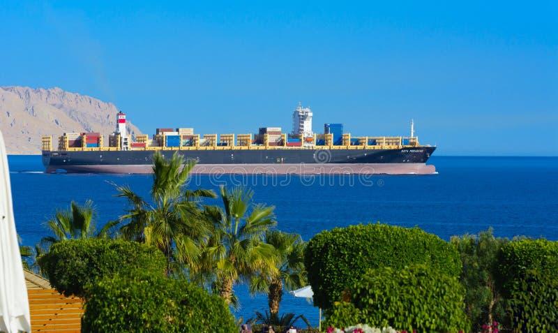 Sharm el-Sheikh, Egipto - 14 de marzo de 2018 Un buque de carga enorme lleva los envases con el cargo en el Mar Rojo contra el ci imagen de archivo libre de regalías