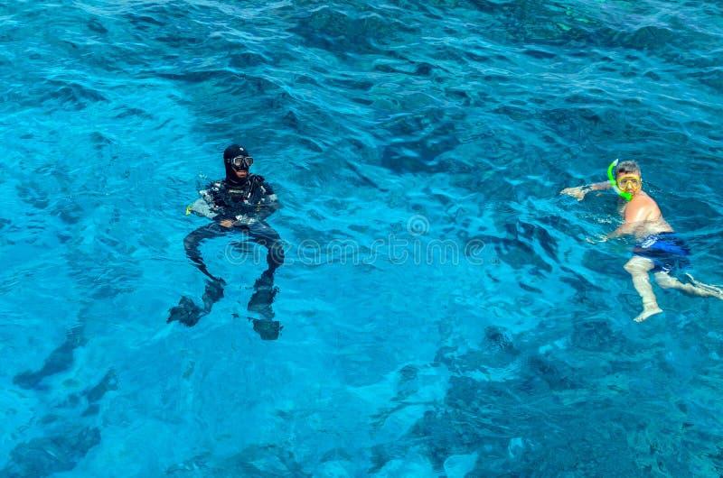 Sharm El Sheikh, Egito, 8 de maio de 2019: Pessoas em engrenagens de snorkeling nadando na água azul clara do mar fotos de stock