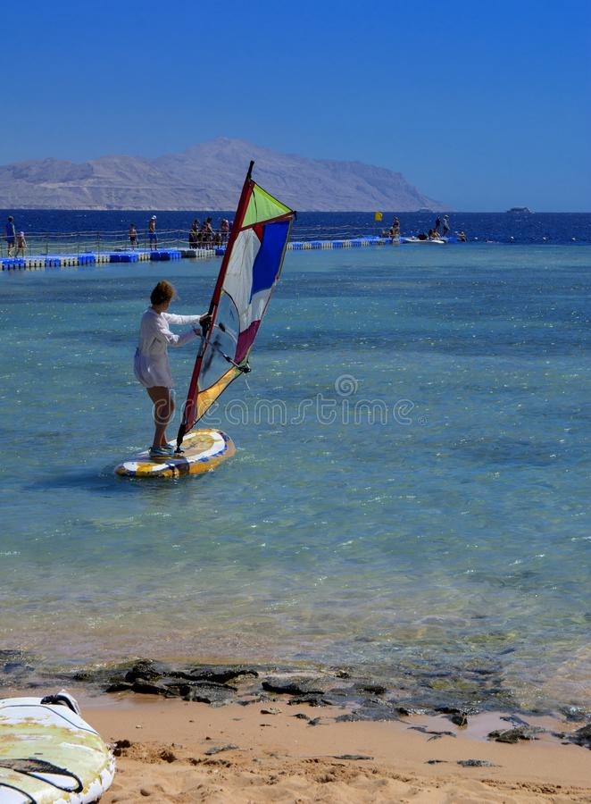 Sharm el-Sheikh, Egito - 14 de março de 2018 Uma menina corre uma placa com uma vela no mastro devido à inclinação e à volta do m foto de stock royalty free